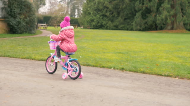 toddler girl ridding  bicycle at winter countryside park,northern ireland - grass family stock videos & royalty-free footage