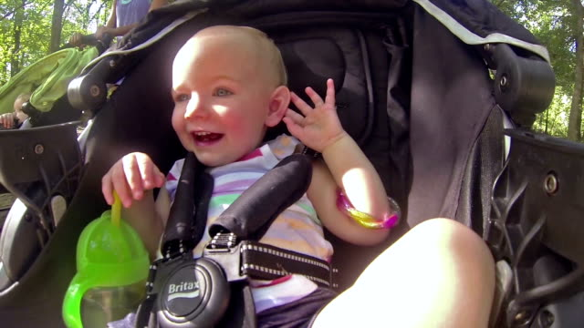 toddler girl riding in stroller as mom walks in park - three wheeled pushchair stock videos & royalty-free footage