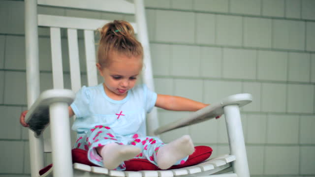 vidéos et rushes de a toddler girl rocks in a rocking chair on a front porch. - bercement