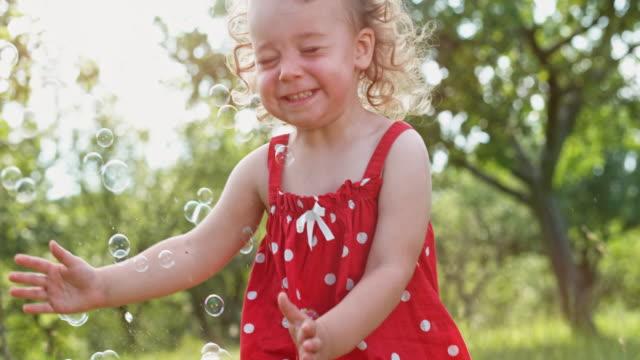 果樹園のシャボン玉の中で実行している slo mo 幼児の女の子 - 幼児点の映像素材/bロール