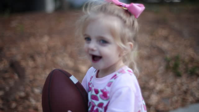 a toddler girl runs around her yard with a football. - girls stock videos & royalty-free footage