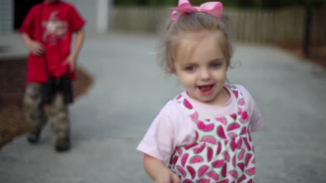 stockvideo's en b-roll-footage met a toddler girl runs on her driveway in pink rain boots. - rubberlaars