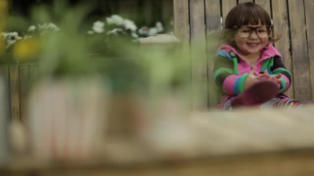 Toddler girl sitting in garden chair