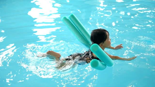 SLO-MO-Kleinkind Mädchen schwimmen mit Nudeln