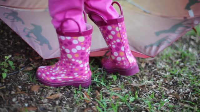 a toddler girl walks around her yard in her pink rain boots. - wellington boot stock videos & royalty-free footage