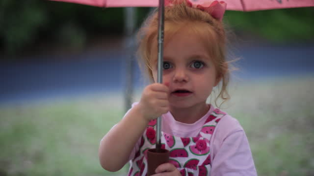 A toddler girl walks around outdoors under a pink umbrella.
