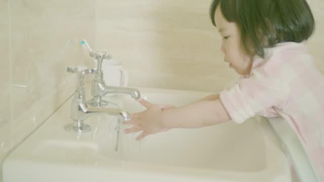 幼児の女の子は自分で手を洗う - お手洗い点の映像素材/bロール