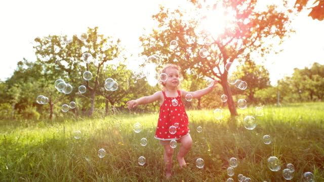 slo mo toddler girl watching soap bubbles shine in the setting sun in the orchard - sapone video stock e b–roll