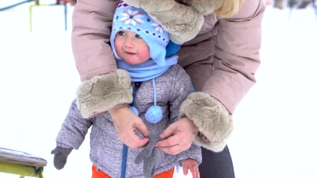 toddler having fun with grandmother in a winter day - warm clothing stock videos & royalty-free footage