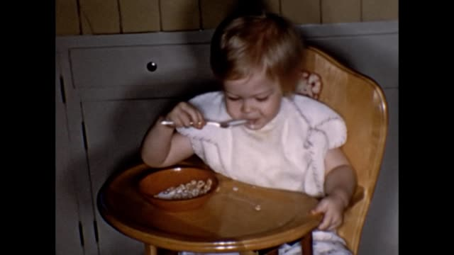 1955 Toddler in High Chair Eating Cheerios Cereal
