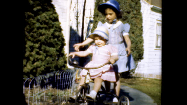 toddler in pink dress carrying basket walks toward camera; toddler in pink attempts to ride tricycle, older girl in blue helps and rides with her - påsk bildbanksvideor och videomaterial från bakom kulisserna