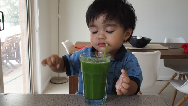 toddler is drinking green smoothie from a straw - kale stock videos and b-roll footage