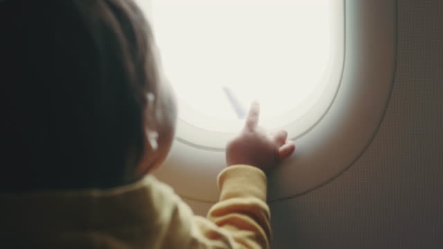 toddler is watching panorama through window airplane - abitacolo video stock e b–roll