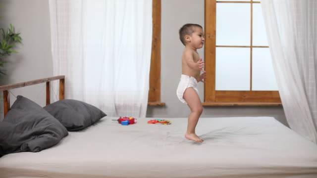 toddler jumping on the bed - nappy stock videos & royalty-free footage