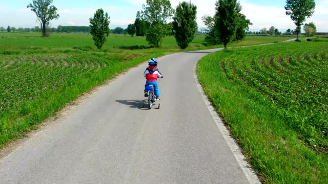 toddler learning to ride his new bicycle - stabilisers stock videos & royalty-free footage