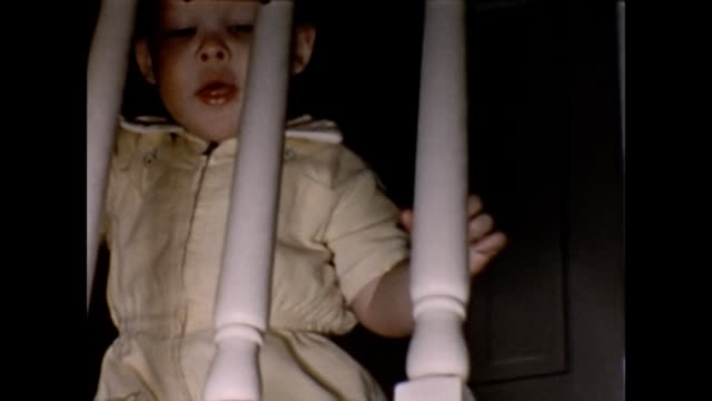 1955 toddler looking through staircase banister railings - endast en flickbaby bildbanksvideor och videomaterial från bakom kulisserna