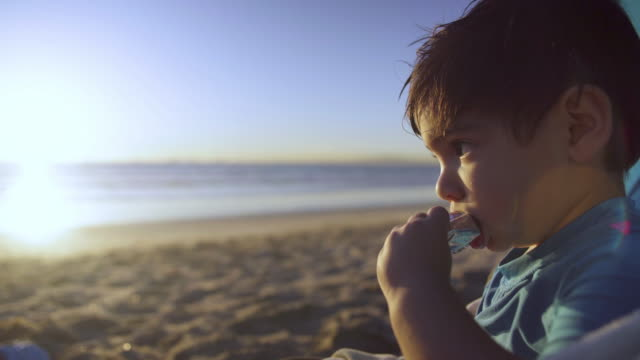 toddler munches on granola bar at the beach - wrapped in a towel stock videos & royalty-free footage