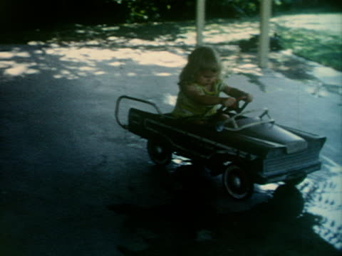 A toddler pedals a little car around a driveway.
