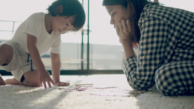 toddler playing jigsaw puzzle with his mother. - jigsaw puzzle stock videos & royalty-free footage