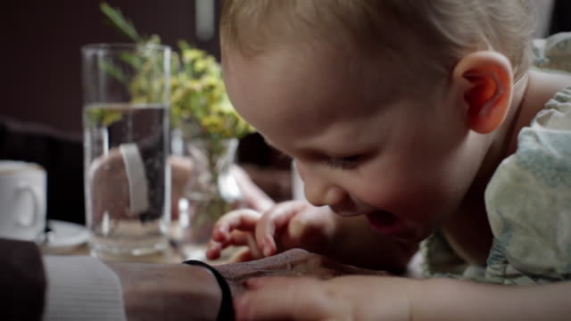 stockvideo's en b-roll-footage met cu pan toddler (18-23 months) playing with grandma hand in café at table / new york city, new york, usa - 18 23 months