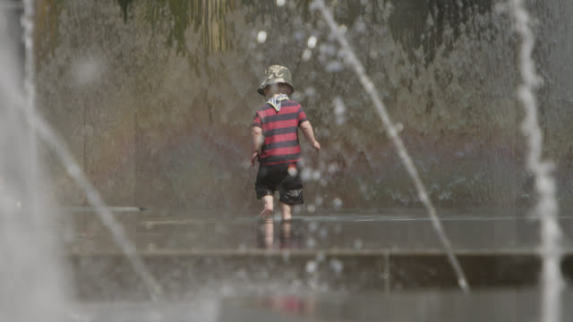 Toddler plays in communal fountains, Bristol, England