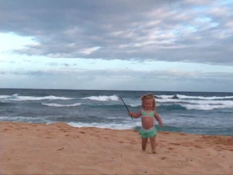 stockvideo's en b-roll-footage met toddler plays on the beach with a stick. - alleen meisjes
