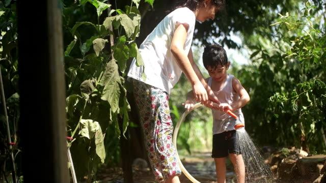 vídeos y material grabado en eventos de stock de el niño juega con manguera de agua al aire libre durante el verano - manguera