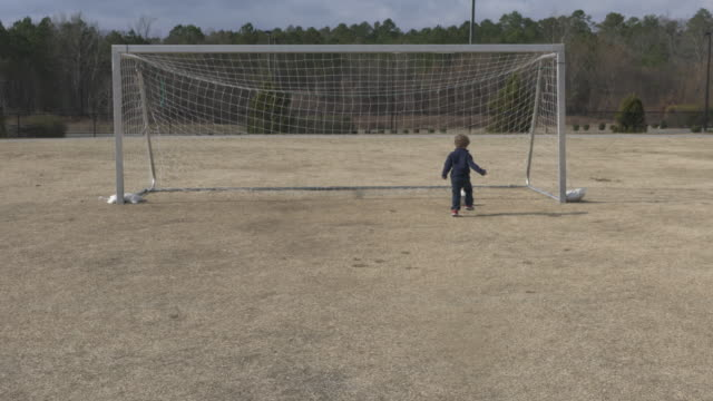 toddler practicing soccer alone - football pitch stock videos and b-roll footage