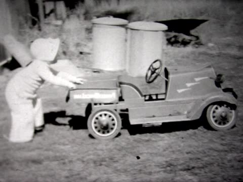 1937 toddler pushes toy fire truck