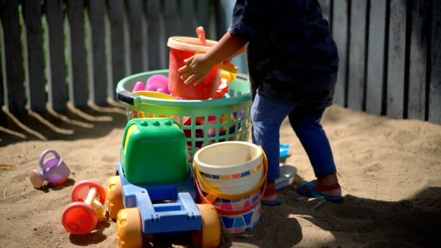 Toddler put away his toys.