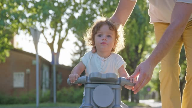 slo mo toddler riding a balance bike with help of parent down a sunny sidewalk - sidewalk stock videos & royalty-free footage