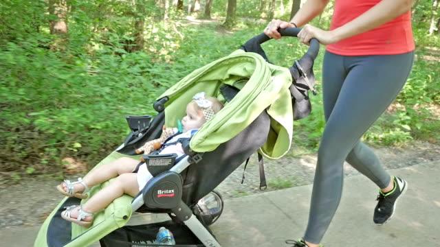 vídeos y material grabado en eventos de stock de niño ciclismo en un cochecito de tres ruedas que mamá se para ejecutar en park - cochecito de bebé