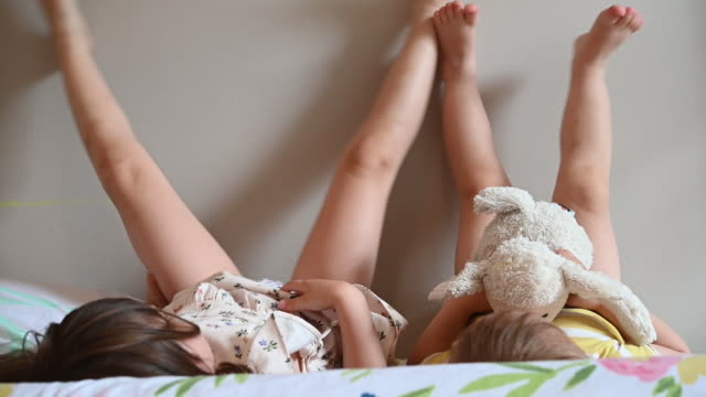 toddler sisters lying on bed with their feet on wall - kleinstkind stock-videos und b-roll-filmmaterial