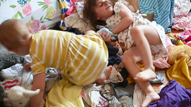 vídeos de stock e filmes b-roll de toddler sisters playing in pile of clothing scattered on bedroom floor - caos
