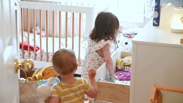 vídeos de stock, filmes e b-roll de toddler sisters throwing clothes from draw onto bedroom floor - 4 5 anos