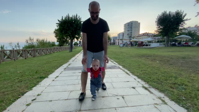 toddler son walking with his father - genderblend stock videos & royalty-free footage