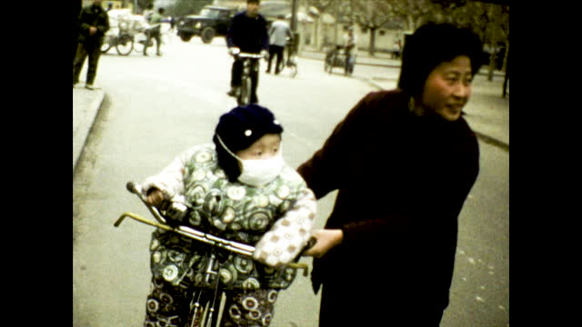 toddler standing with a toy gun looking confused; bundled up toddler with face mask sitting on a bicycle pushed by a smiling woman, busy street in... - toy gun stock videos & royalty-free footage