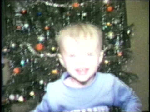 a toddler stands in front of a christmas tree. - home movie stock videos & royalty-free footage