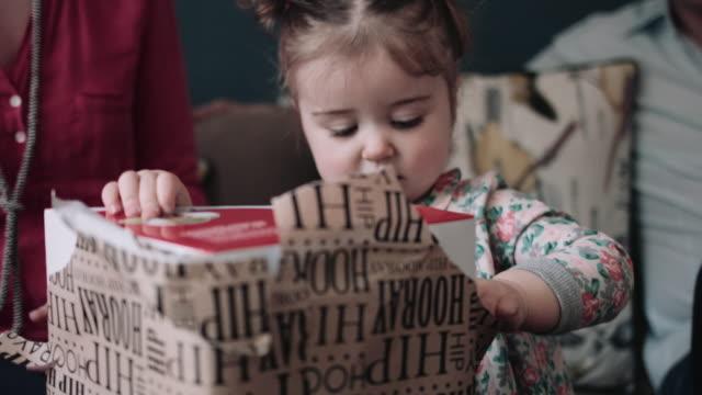 stockvideo's en b-roll-footage met toddler unwrapping birthday present - verjaardagskado