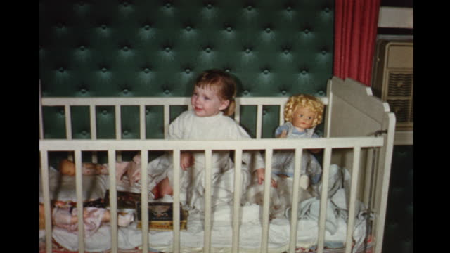 1956 HOME MOVIE Toddler waking up in crib, petting cat and playing with dolls / Toronto, Canada