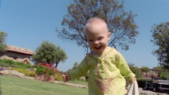 stockvideo's en b-roll-footage met toddler walking across lawn / sardinia - alleen jongens