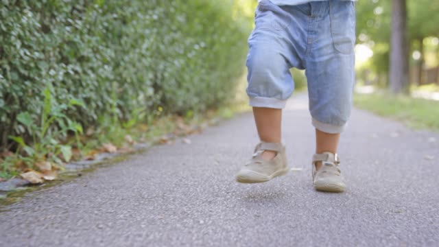 slo mo toddler walking down a sidewalk - shorts stock videos & royalty-free footage