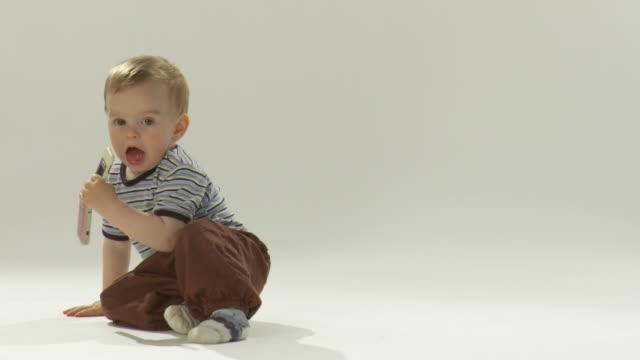 vídeos de stock e filmes b-roll de hd: criança pequena com um telemóvel - sitting