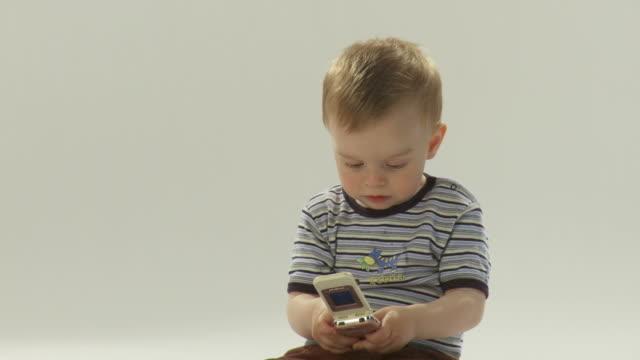 vídeos de stock, filmes e b-roll de hd: bebê com um telefone móvel - só um bebê menino