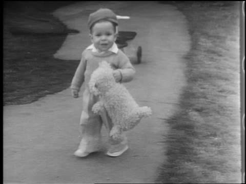 B/W 1944 PAN toddler with stuffed animal walking on sidewalk / looks at camera + smiles / home movie