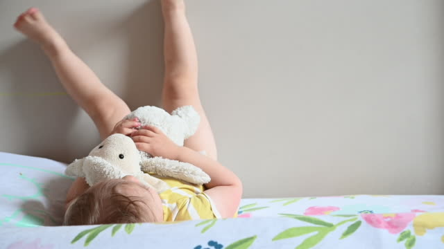toddler with stuffed animal with feet on wall rolling off bed - piedi alzati video stock e b–roll