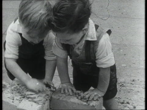 Toddlers patting cement onto bricks