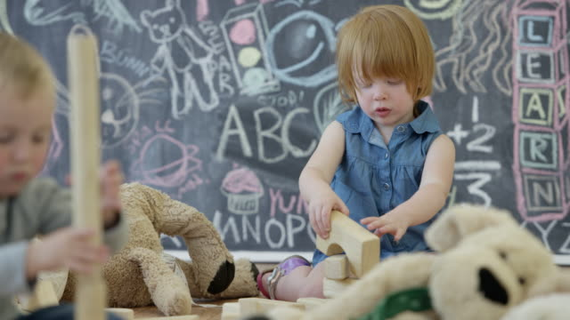 Toddlers Play with Toy Blocks in a Daycare