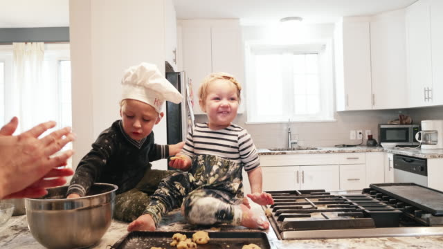 vídeos y material grabado en eventos de stock de niños pequeños sentados en el mostrador de la cocina jugando con la masa de galletas - messy