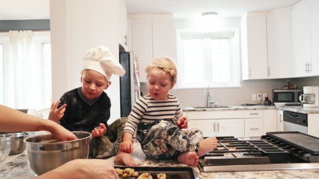 toddlers seated on the kitchen counter playing with the cookie dough - sorella video stock e b–roll